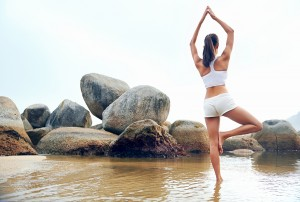 yoga beach woman doing pose at the ocean for zen health and peac